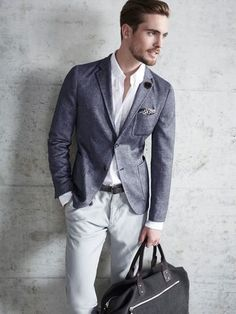Dress in a charcoal blazer and grey pants for a seriously stylish look. Shop this look on Lookastic: https://lookastic.com/men/looks/blazer-dress-shirt-chinos/18968 — White Dress Shirt — Black Lapel Pin — Beige Print Pocket Square — Charcoal Blazer — Black Leather Belt — Grey Chinos — Black Canvas Duffle Bag