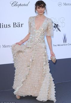 Striking: Milla Jovovich opted for an unusual ruffle-detail taupe dress with dramatic silver adornment