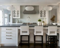 Beautifully decorated white and gray kitchen features three Foscarini Caboche Grande Chandeliers hung above a white island topped with Pietra Cardosa Soapstone countertops fitted with a sink and polished nickel gooseneck faucet and seating three white leather cut out counter stools .