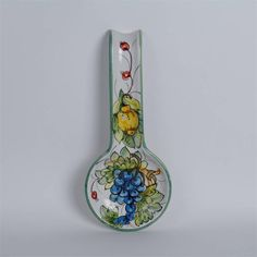 Spoon Rest - Bacche $34.95 Beautiful Bacche spoon rest is skillfully crafted by a multi-generational family of artisans in a small town outside of Florence, Italy. Each ceramic piece is a unique work of art; no two are alike. •Dimensions: 11 inches length, 4 3/4 inches wide, 1 1/4 inch depth •Pottery glazed with Maiolica  •Handmade and painted in Italy •Lead free •Food safe, hand washing recommended •Two holes for hanging.