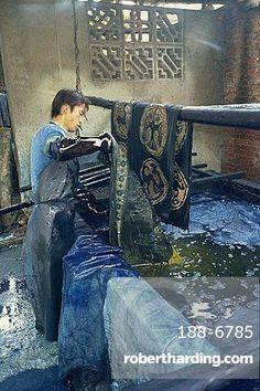 Dipping batik in an indigo vat, Guizhou, China. Photo: Robert Harding