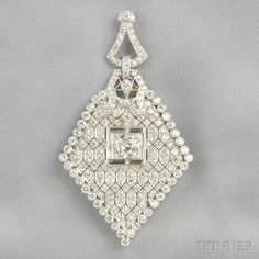 Art Deco Platinum and Diamond Pendant, set with an old European-cut diamond weighing approx. 1.40 cts., further set with baguette-, old European-, and transitional-cut diamonds, approx. total wt. 7.00 cts., synthetic gem-set Masonic star accent, (one stone missing), lg. 3 in.