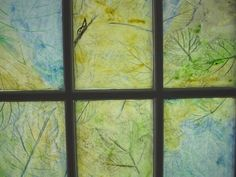 """Leaf rubbing stained glass.  Use dark-colored crayons to rub leaves on paper, paint with light-colored watercolors, """"paint"""" with oil on back to make more transparent.  It will stick to the window with the oil or use tape if necessary."""