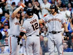 San Francisco Giants Andrew Susac , left, high fives San Francisco Giants Joe Panik with Michael Morse, right, after they score on a Travis Ishikawa double in the second inning of a baseball game against the Chicago Cubs on Wednesday, Aug. 20, 2014, in Chicago. (AP Photo/Matt Marton)