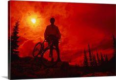 Sun behind cyclist on hill