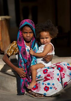 Worried teenage girl holding little baby in hands while seated on stair, Lamu, Kenya Out Of Africa, East Africa, Kenya Africa, We Are The World, People Of The World, Lamu Kenya, Little Babies, Little Girls, African Life