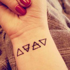 Wrist tattoo of the alchemic symbols of four basic elements.
