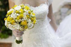 Bellissimo Bouquet da sposa giallo e bianco tenuto in mano con sfondo abito
