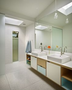 In the kids' bathroom, a colorful custom vanity complements the clean, white palette. Mirrors extend up into a skylight to draw light in over the vanity.