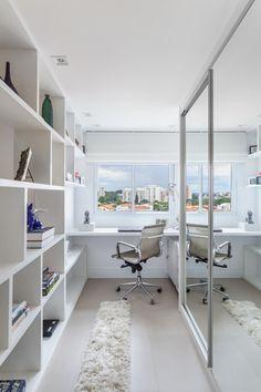 O armário espelhado e a tonalidade clara predominante criam sensação de amplitude no home office localizado no final de um corredor. Projeto da arquiteta Marcy Ricciardi.