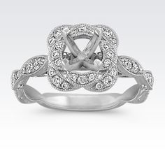 The unique scalloped edges of this ring extend to the top of the design and form a halo to surround the center 0.75 carat round diamond of your choice. With 46 round diamonds, at approximately .31 carat total weight, pavé-set in quality 14 karat white gold, this ring is a gorgeous backdrop that is sure to be cherished. This engagement ring also emits a lovely vintage inspired style.  Part of our Hollywood Glam Collection.