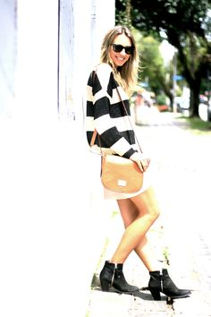 Gold/black striped sweater, white skirt, and classic bag.