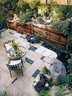 Add style to small spaces by mixing complementary paving materials together. In this tiny backyard, irregular shape bluestone slabs are highlighted with pockets of polished blue-gray river rock.