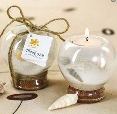 Un recuerdo de boda que además puede ser centro de mesa es una pecera con arena, conchitas y una vela http://www.bodasmargarita.net