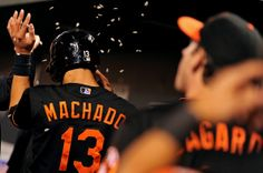 Manny Machado #13 of the Baltimore Orioles is greeted in the dugout after scoring off of a Adam Jones #10 (not pictured) hit in the seventh inning against the Oakland Athletics at Oriole Park at Camden Yards on August 23, 2013 in Baltimore, Maryland. The Baltimore Orioles won, 9-7.