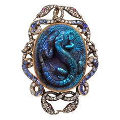 Estate Betteridge Collection Labradorite Salamander Brooch with Diamond  Antique carved labradorite salamander brooch, mounted in pink gold, the oval-shaped labradorite surrounded by entwined snake motifs set with rose-cut diamonds and sapphires, the snakes with rose-cut ruby eyes.