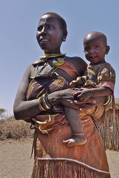 Africa | Portrait of a Datoga woman wearing traditional clothes carrying her child, Tanzania | © Rita Willaert