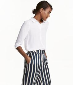White. Straight-cut, long-sleeved blouse in woven fabric with a collar. Concealed buttons at front, button at cuffs, and rounded hem. Slightly longer at