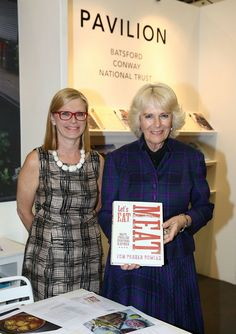 Polly Powell and Camilla, Duchess of Cornwall with an advance copy of 'Lets Eat Meat' by Tom Parker-bowles during an official visit to The London Book Fair at Earls Court on April 9, 2014
