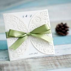 white laser cut wedding invitations with sage green ribbons
