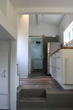 An 8×24 ft. tiny home featuring a loft walkway, floor storage, and a large bathroom. A living room with couch and entertainment center fits under the loft.