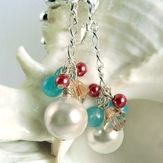 These dangly cluster earrings include a large white glass pearl topped by rose-pink crystals, deep pink pearls, and blue glass beads. The chain is silver plated, as are the leverback earring hooks. Jewelry Design Earrings, Gems Jewelry, Bead Earrings, Jewelry Crafts, Jewelry Ideas, Designer Earrings, Wire Jewelry, Golden Jewelry, Handmade Beaded Jewelry