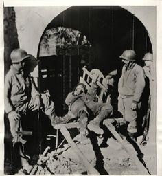 1944- American troops entering San Vittore, Italy, pass the body of a German soldier killed in action.