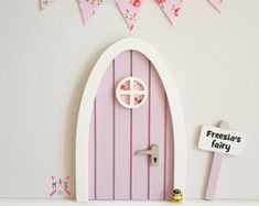 Miniature Pink Fairy door - a cute personalised fairy door in blossom pink, a lovely gift for girls and beautiful for a girls room. Great for make believe and pretend play. Ideal way to build on the tooth fairy tradition. Let the magic in.... Make your home a fairy house.  Capture the imagination of your little one with this cute little personalised fairy door. Made from wood and hand painted in blossom pink, with white frame and round window. Then finished with a tiny silver painted door…