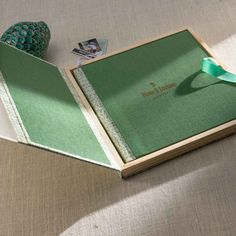 An album for keepsake. This innovative handcrafted album comes with a wooden case enclosed with a half side translucent acrylic front and half side premium cloth material.
