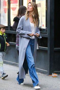 Look despojado de Gisele Bundchen usando t-shirt, jeans, maxi casaco e tênis branco