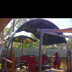 Deck cover made out of a trampoline, tarp and bungee cords! Using half of an old trampoline frame, a tarp and some bungee cords a fabulous deck cover was born!