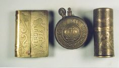 "Three lighters. Left: Book type lighter made from scrap brass. Engraved 'Verdun 1918' with zig-zag work background. Reverse side with floral work and shield and zig-zag background. 2 5/8"" long by 13/4"" wide. Center: Round lighter made with round 'Gott Mit Uns' roundels from German belt buckles. 21/2"" high by 2"" wide. Right: Cartridge lighter made from small cartridge or rifle cleaning kit cylinder. Engraved on bottom half ' H L' with floral motif and'1914 15  16 17' in four-leaf clover with…"