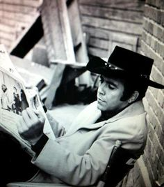 Pernell Roberts reading a newspaper on the set of Bonanza.