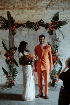 Orange Wedding Suit for Groom and White Sari for Bride | By Millar Cole Photography | Vibrant Wedding | Colourful Wedding | Tropical Wedding Flowers | White Sari for Wedding | Orange Wedding Suit | Legnhas for Bridesmaids | London Wedding | Industrial Wedding | Neon Wedding Signs Wedding Ceremony Arch, Wedding Sari, Wedding Suits, White Wedding Flowers, Orange Wedding, Wedding Colors, White Sari, London Wedding, Industrial Wedding