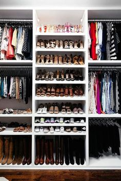 White walk-in closet features low built-in boot shelves positioned beneath stacked shoe shelves flanked by clothes hanging from Joy Mangano Black Huggable Hangers.