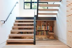 Built in book shelves under the staircase for kids -  Thoughtful Design Details Warm Up a Modern Family Home in Northern California - Dwell