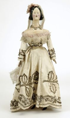 """probably early 20th century, papier mache shoulder head with fancy molded hair and painted molded features, cloth body with wooden limbs, dressed in cream satin gown with metallic trim, 21.5"""" t."""