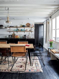 Rug in kitchen dining area / wood / black / white / flashes of colour / cool chairs & table