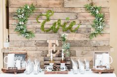 Adventure, outdoorsy themed baby shower. Rustic backdrop with greenery. Cold brew coffee table. #rusticbabyshower #babyshower #rusticbackdrop