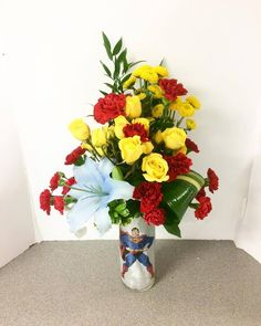 Custom superman arrangement. Spray roses, mini carns and lilies sprayed blue.