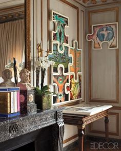 A collection of Francesco Clemente drawings hangs above an antique Italian console.