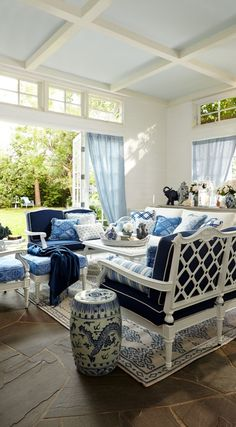 Blue and white open-air living: stone floor, french doors, wrought iron in white, and a light blue ceiling in Ralph Lauren blue and white fabric