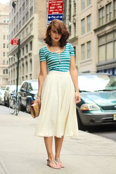 R&B pkng. sign, asymmetric wavy aburn hair, teal/cream striped U-neck quarter-sleeve top, cream midi skirt, sandals, red lips, pink fingernails, teal car, cream building façades & sidewalk