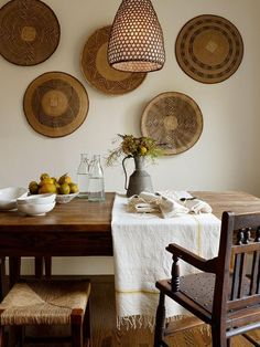 The dining area is decorated with a collection of African platters from Floreal in San Francisco. The dining table and bench are custom-made from reclaimed pine by Peterson Antiques in LA; the 19th-century rush stools are from Nicky Kehoe.