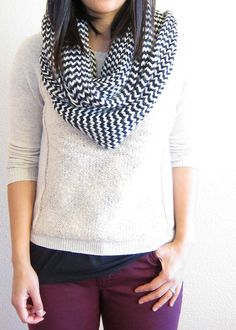 Cream-colored sweater over a black tee, burgundy skinnies + black and white infinity scarf and black boots