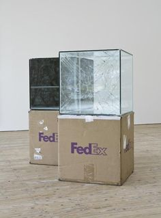 Glass cubes travel via FedEx from exhibition to exhibition, inevitably being damaged on route and displayed on shipping box pedestals.  by Walead Beshty