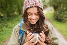 smiling young woman with cup and backpack hiking | www.superimagemarket.com