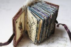 """Alice in Wonderland mini book (2 1/2"""" x 1 3/4"""" x 2"""") ~ """"made from polymer clay modeled from an antique matchbox holder. The front cover has a tiny keyhole with a picture of Alice herself and various brass findings and chain. The paper signatures inside are made from Graphic 45's new Alice in Wonderland paper collection and various stamped images of the characters."""" ~ by Sarah Fawcett, Etsy (2nd of two pins)"""