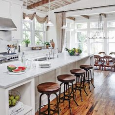 Buttboard walls, a metal roof, tongue-and-groove ceilings, and reclaimed woods, including hand-hewn beams salvaged from an old mill and vintage timber, give this kitchen Lowcountry character.