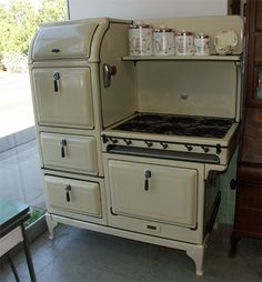 """From the 1930's, this Magic Chef features 6 burners, a double oven, warming oven, storage drawer, and shelf. It is cream colored with black trim, and come with a custom vent hood. It measures 53"""" wide x 64"""" tall."""